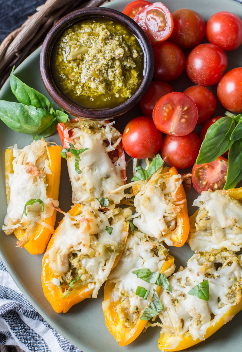 Chicken-stuffed peppers on a plate with cherry tomatoes.