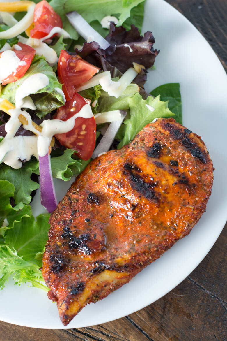 blackened chicken breast on white plate with a side salad