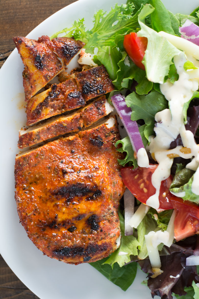 overhead view of partially sliced grilled blackened chicken breast on a white plate with a side salad