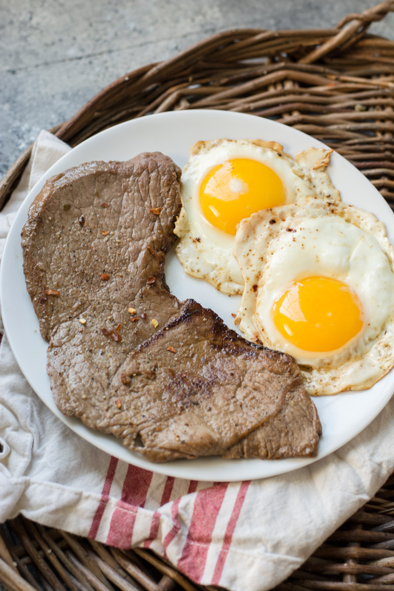breakfast steak and eggs on a white plate. The plate is on a tea towel, which is on a wicker tray