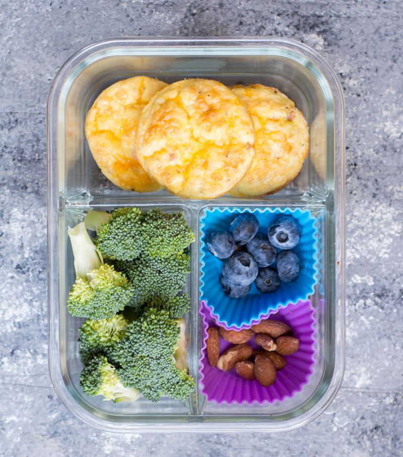 overhead view of a meal prep container with three low carb egg muffins, broccoli, berries, and nuts.