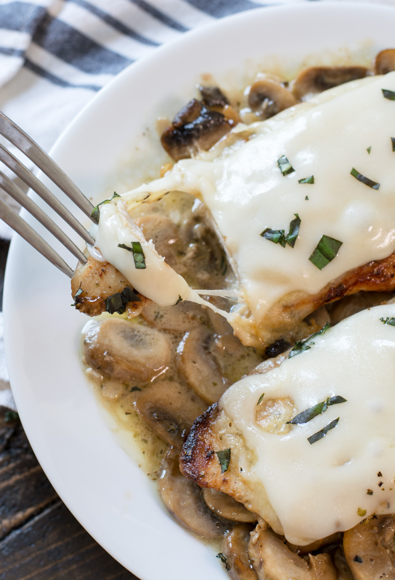 Two chicken breasts with mushroom sauce on a white plate. A piece is being removed by a fork.