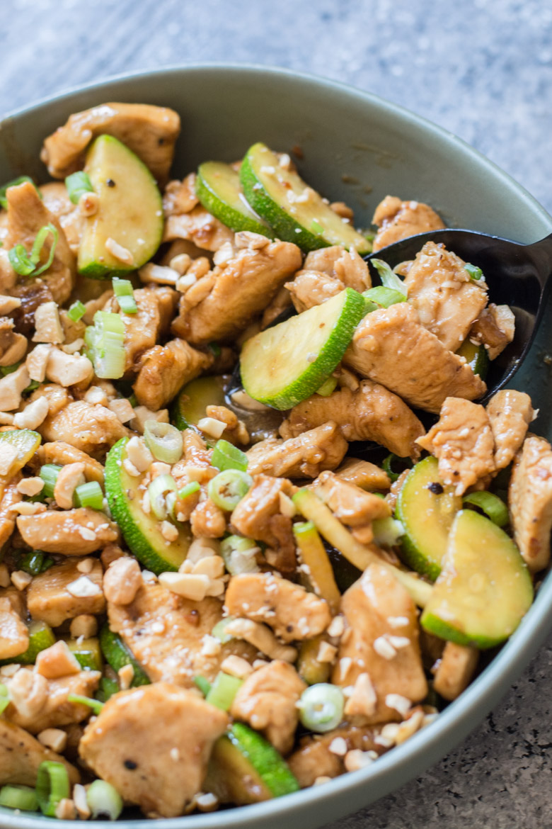 sesame chicken and zucchini keto stir fry in a large gray bowl with a spoon