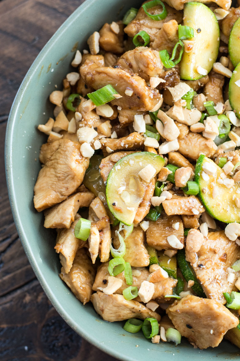 chicken and zucchini low carb stir fry in a bowl, garnished with green onions and cashews