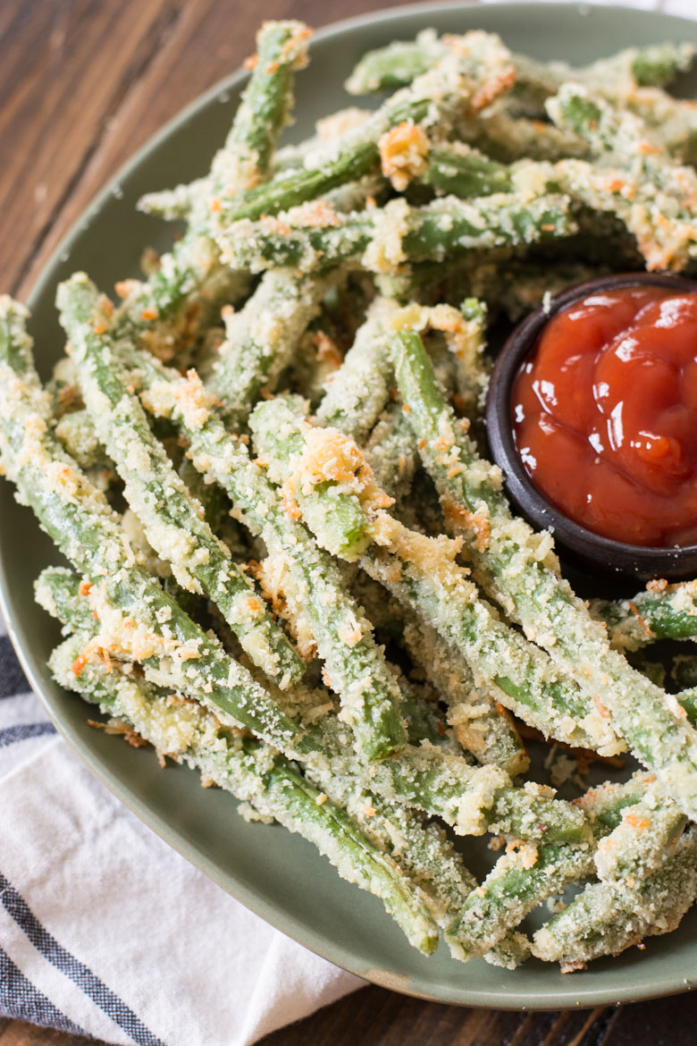 healthy green bean fries on a large plate with a dish of ketchup