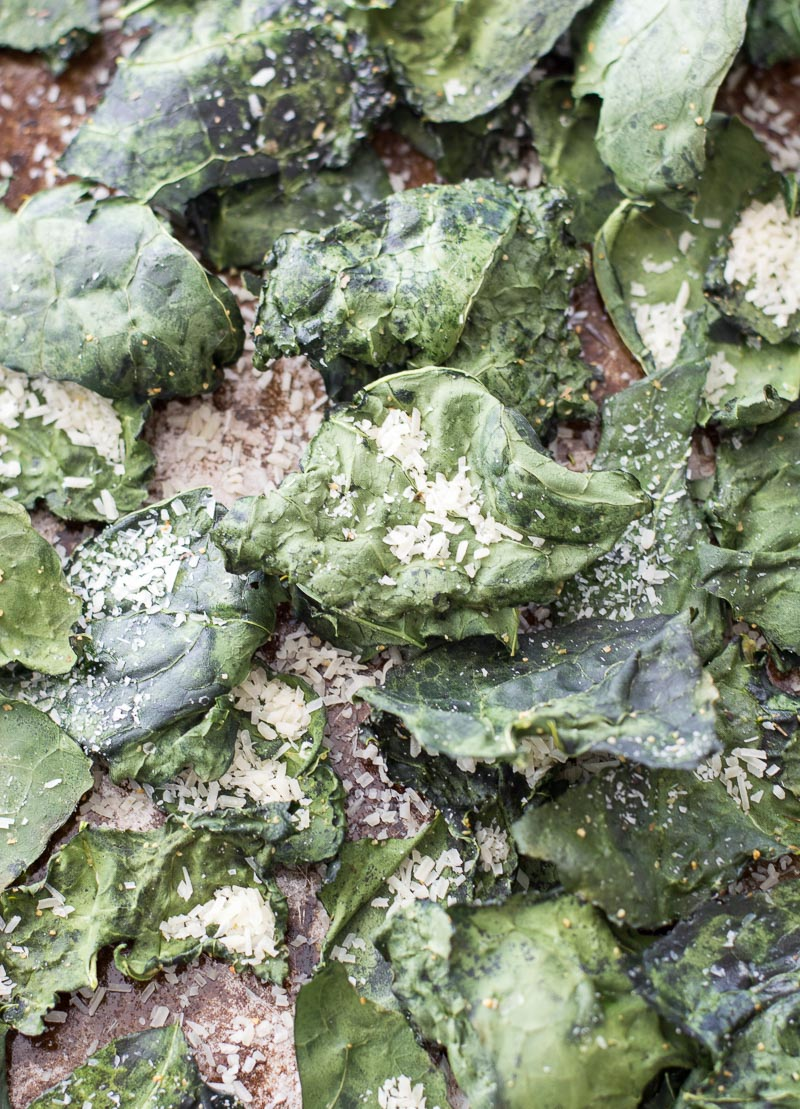 Overhead view of roasted kale chips topped with parmesan