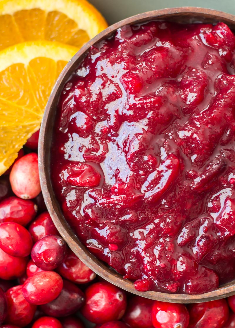 overhead view of keto cranberry sauce in a wood bowl next to orange slices and fresh cranberries