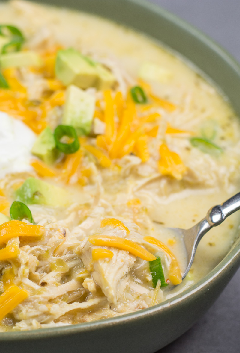 This Keto White Chicken Chili is loaded with shredded chicken, chilis, peppers and cauliflower rice! At about 7.5 net carbs per heaping serving this is the ultimate creamy keto comfort food!