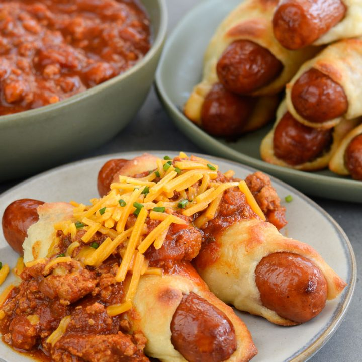 These Keto Chili Cheese Dogs have everything you love about this classic, without the carbs! Easy, low carb, gluten free pigs in a blanket are smothered with keto chili and shredded cheddar cheese! For about 5 net carbs per serving this is a low carb recipe you will love!