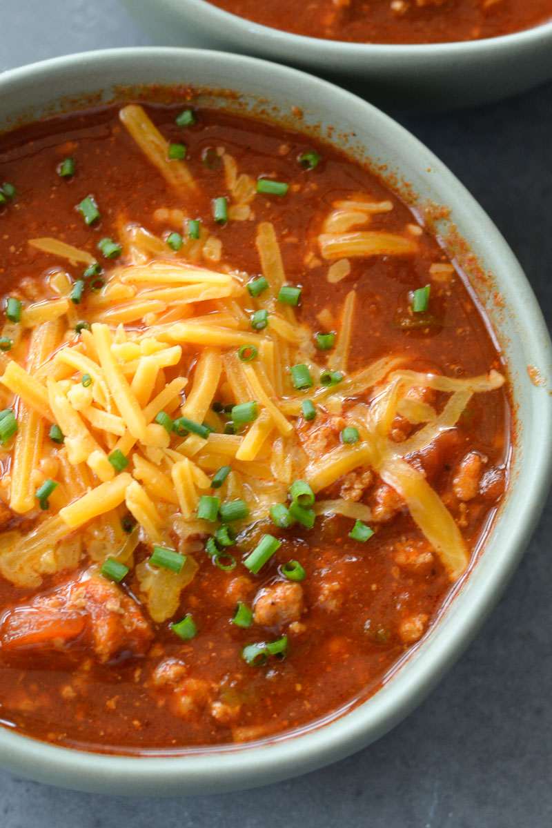 Overhead view of no bean chili in a bowl, topped with chives and shredded cheddar cheese.
