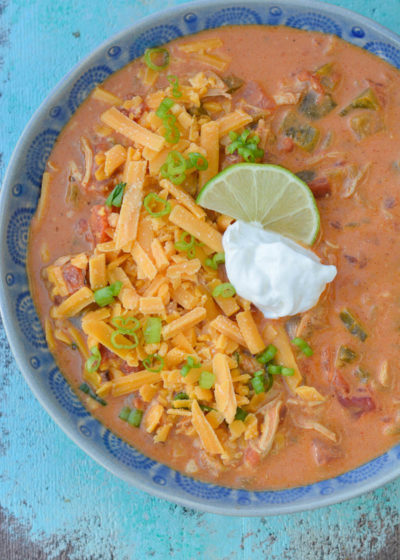 This Keto Cheesy Chicken Enchilada Soup has just about 6 net carbs and is super creamy! Top with shredded cheese, sour cream, green onions, and a squeeze of lime to bring it over the top!