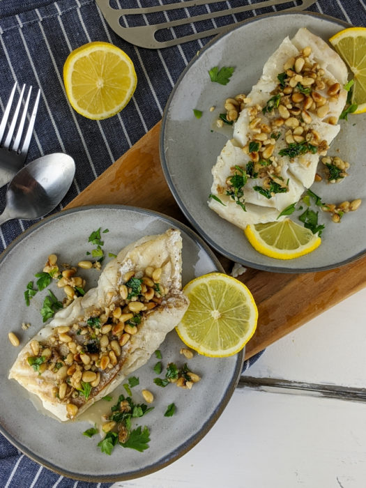 This keto-friendly cod recipe is covered in toasted pine nuts and drenched in a delicious lemon, garlic sauce.